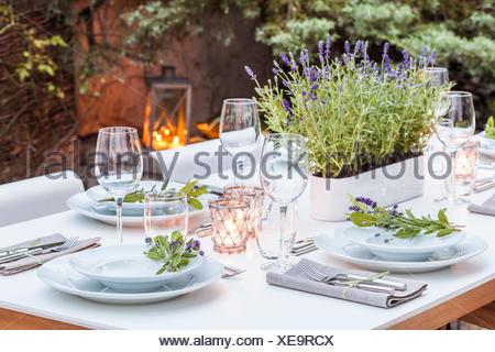 Deutschland, Garten, Terrasse, Holzdeck, Gartenmöbel, moderne Sitzgruppe, gedeckter Tisch, festlich, Tischdeko Lavendel, Lichter - Stock Photo