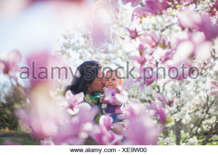 Granddaughter and grandmother amongst magnolia blossom - Stock Photo