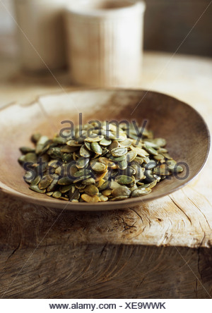 Wooden bowl of pumpkin seeds - Stock Photo