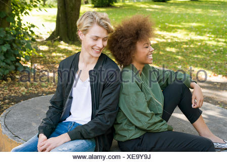 Sweden, Vastra Gotaland, Young smiling couple sitting in park - Stock Photo