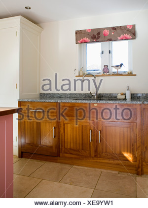 dark modern country kitchen.  Floral blind on small window above sink in modern country kitchen with dark wood fitted units