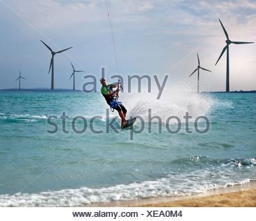 Croatia, Zadar, Kitesurfer jumping in front of wind turbine - Stock Photo