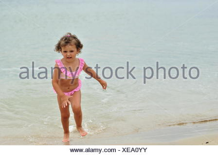 Girl in pink bikini running out of sea - Stock Photo