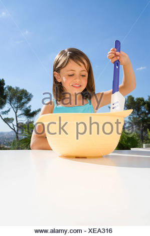 Young girl stirring cream in a bowl - Stock Photo