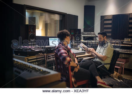 Music producers talking in recording studio - Stock Photo