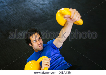 Man on back lifting kettlebells - Stock Photo