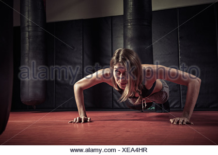 Woman doing push ups in gym - Stock Photo