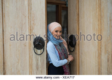 Portrait of a woman wearing a hijab standing in a doorway - Stock Photo