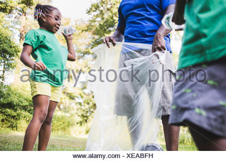 Father picking up litter with son and daughter at eco camp - Stock Photo