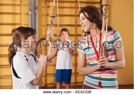 Germany, Emmering, Woman and girl holding gymnastic rings with boy in background - Stock Photo