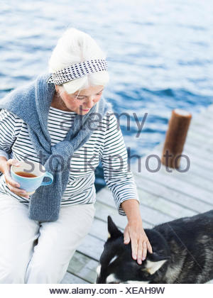 A senior woman and a dog on a jetty. - Stock Photo