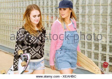 Two young women carrying skateboards beside glass wall - Stock Photo