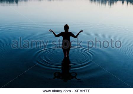 Woman meditating in peaceful lake - Stock Photo