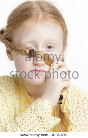 Girl, 8 years old, holding a braid in front of one of her eyes - Stock Photo
