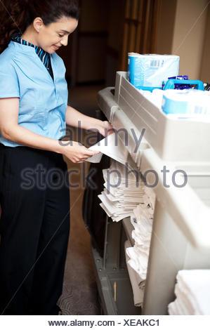 Back-office female employee folding sheets. Arranging everything neatly in cart - Stock Photo