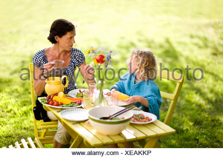 Mother and daughter eating outdoors - Stock Photo