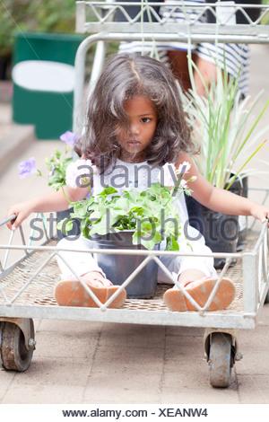 Girl sitting in cart at flower nursery - Stock Photo