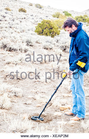 Man using metal detector in Black Rock desert, Nevada, America, USA - Stock Photo