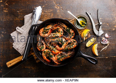 Tiger prawns shrimps roasted on frying grill pan with green sauce, lemon and garlic on wooden background - Stock Photo