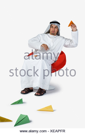 Young man playing with paper planes - Stock Photo