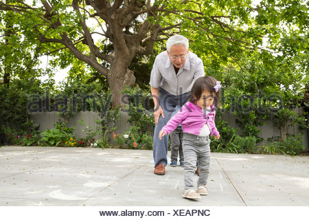 Grandfather playing hopscotch with toddler granddaughter - Stock Photo