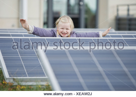 A young girl standing amongst solar panels - Stock Photo