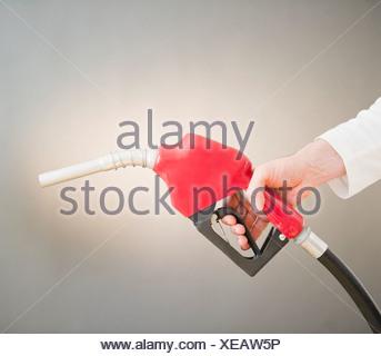 Hand holding fuel pump - Stock Photo