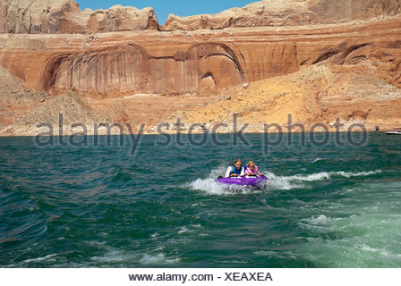 Mother and daughter ride on purple towable tube behind speedboat on lake powell; page arizona usa - Stock Photo