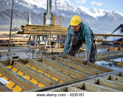 Construction worker lifting shuttering wall with crane, preparing framed formwork, Innsbruck Land, Tyrol, Austria - Stock Photo