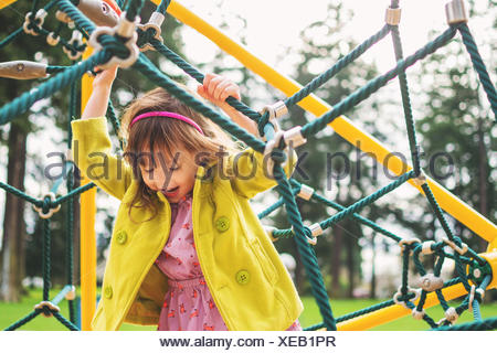 Girl playing on climbing ropes in playground - Stock Photo