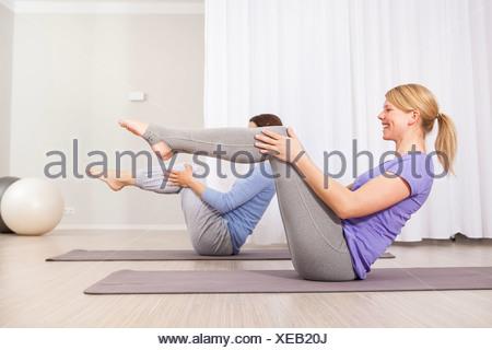 Two women doing Pilates exercise - Stock Photo