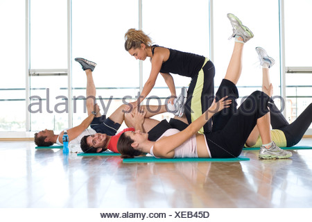 Female fitness instructor teaching class in studio in gym, hand on man's leg, portrait of man smiling - Stock Photo