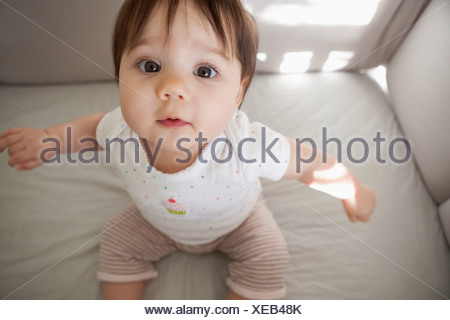 Baby girl sitting up in crib - Stock Photo