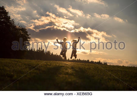 Silhouettes of two children jumping side by side on a meadow at backlight - Stock Photo