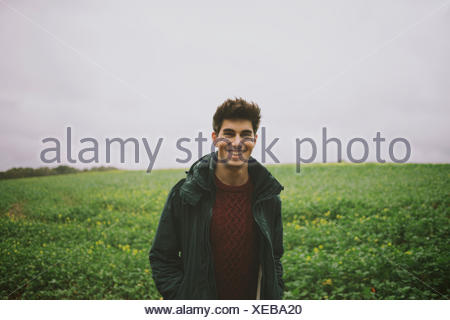 Portrait of smiling young man standing in field - Stock Photo