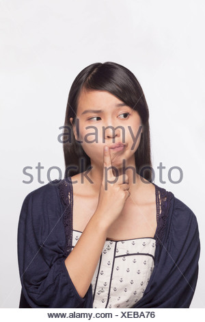 Young woman with finger to her mouth contemplating, studio shot - Stock Photo
