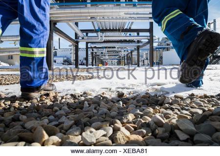 Workers walking snowy rocks below gas plant pipeline - Stock Photo