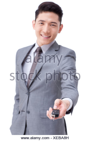 Young businessman with car key - Stock Photo