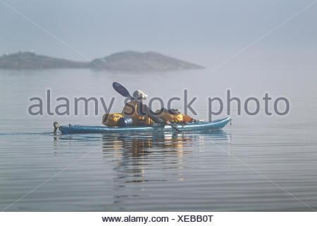 Kayaking in the fog on Lake Superior, Lake Superior Provincial Park, Ontario, Canada - Stock Photo