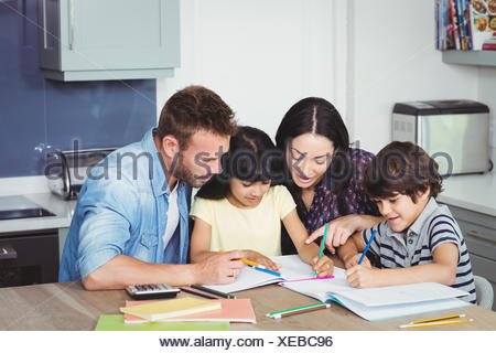 Parents helping children in doing homework - Stock Photo