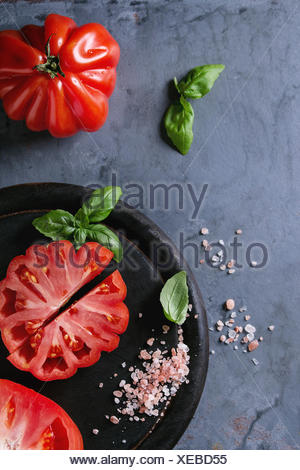 Whole and sliced organic tomatoes Coeur De Boeuf. Beefsteak tomato with pink salt and basil on black wooden chopping board over blue gray metal textur - Stock Photo