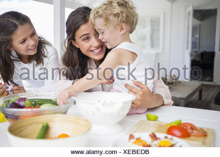 Happy young family preparing vegetables at home - Stock Photo