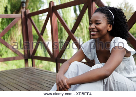 Young African woman sits on a wooden deck