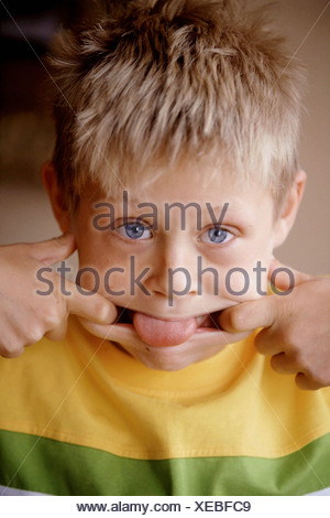 Male child blonde spiky hair wearing yellow and green t shirt fingers pulling each side of mouth tongue sticking out thumbs in - Stock Photo