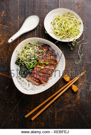 Rice noodles bowl with Peking Duck and sprouts on wooden background - Stock Photo