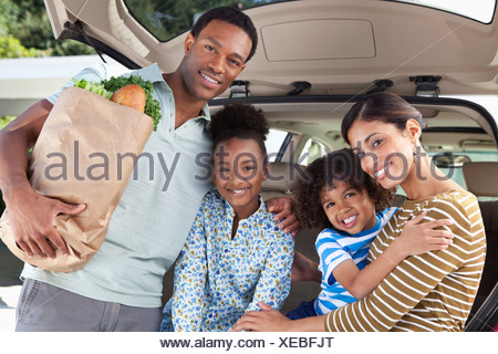 Family unloading groceries from car - Stock Photo
