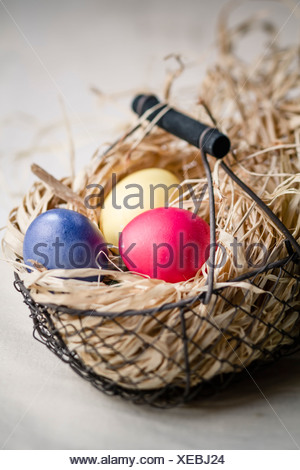Three coloured easter eggs in basket filled with straw, close up - Stock Photo