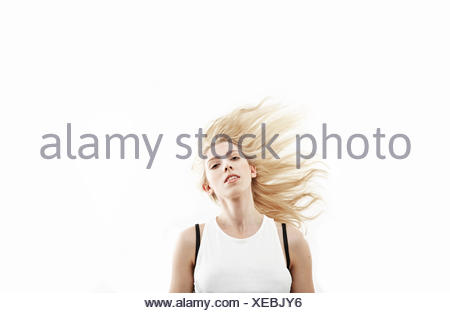 Studio portrait of young woman shaking long blond hair