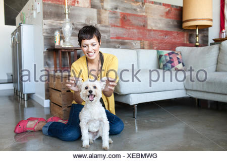 Young woman holding up dogs ears in living room - Stock Photo