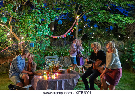 Three couples having fun at garden party at night - Stock Photo